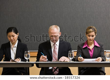 Busy co-workers meeting at table in conference room - stock photo