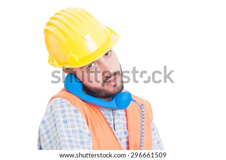 Busy constructor or builder holding phone between ear and shoulder wearing yellow helmet and vest - stock photo
