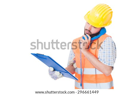 Busy contractor using phone while holding clipboard. Support or assistance for construction company - stock photo
