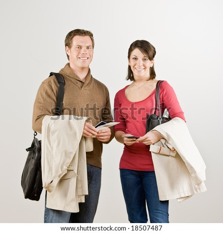 Busy couple preparing to travel with airline tickets, coats and briefcase - stock photo