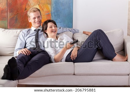 Busy couple watching tv after work, horizontal