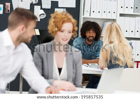 Busy day at the office with a selective focus image of two businesspeople having a discussion at the back of the office while a young man and woman work in the foreground - stock photo