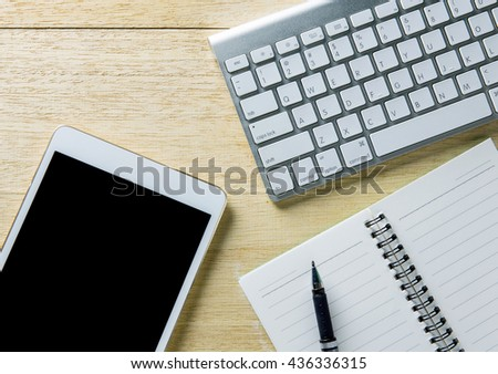 Busy desk of a businessman with an open diary and tablet.