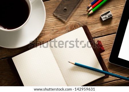 Busy desk of a university student with an open agenda ready to be filled-in. - stock photo