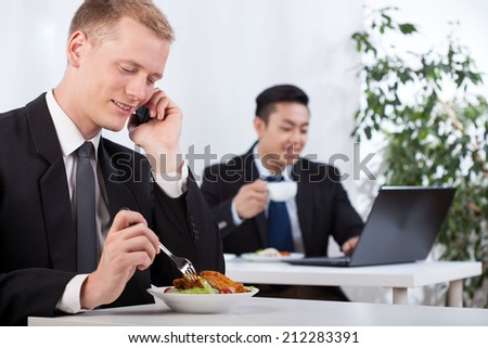 Busy diverse businessmen eating lunch in office - stock photo