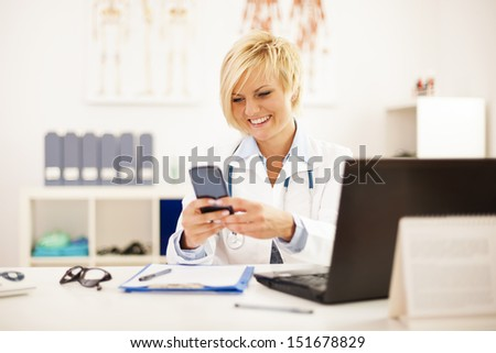 Busy doctor at her office - stock photo