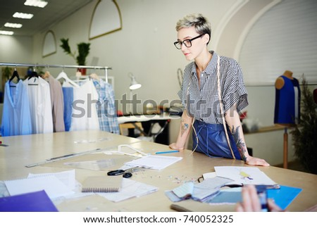 Busy dressmaker standing by workplace and thinking of new ideas of clothes