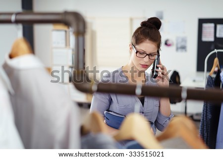 busy fashion designer talking on the phone in the studio with a worried facial expression