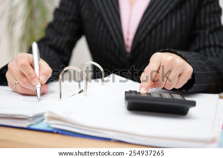 Busy female accountant working with documents - stock photo