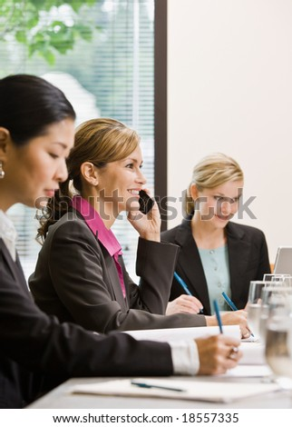 Busy female co-workers meeting at table in conference room - stock photo