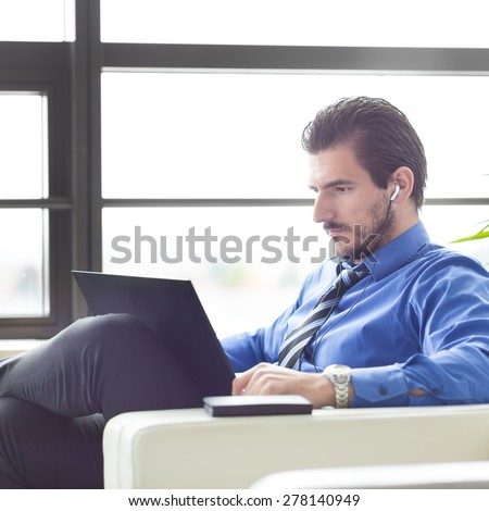 Busy, focused businessman in office working on his laptop wearing headphones. Side view.  - stock photo