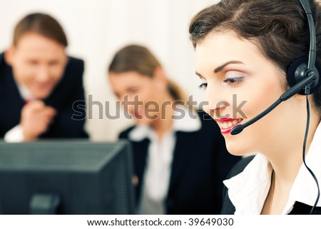 Busy group of people, in the foreground customer care representative, in the background businesspeople looking at a computer screen - stock photo