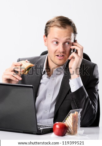 Busy hardworking business man eats lunch at his desk while working and talking on his mobile cell phone - stock photo