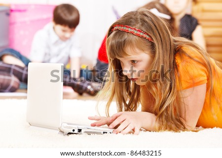 Busy kid lie watching laptop screen - stock photo