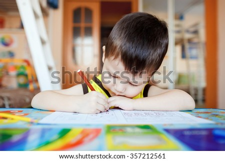 Busy little boy drawing with felt pens at home with colorful interior, three years old. - stock photo