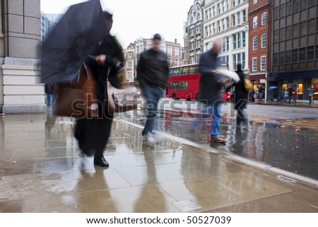 Busy london commuters in the pouring rain with umbrellas and coats - stock photo