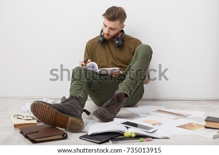 Busy male student wears casual clothes and boots, writes notes, being invlolved in studying before session. Creative young writer has inspiration, sits on floor, put down notes in diary, isolated
