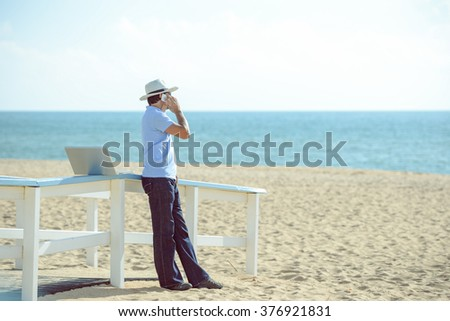 Busy male working on the laptop and talking on mobile. Man in hat speaking on smartphone over blue sky and ocean beach background - stock photo