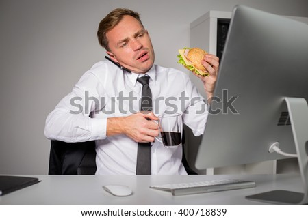 Busy man at the office having coffee and burger  - stock photo