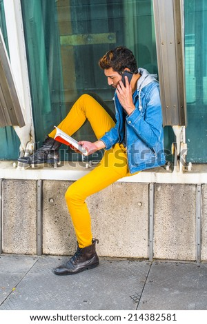 Busy Man. Dressing in a blue jacket with hood, yellow pants, leather boot shoes, a young handsome guy is sitting by a metal structure, reading a book and making a phone call in the same time.