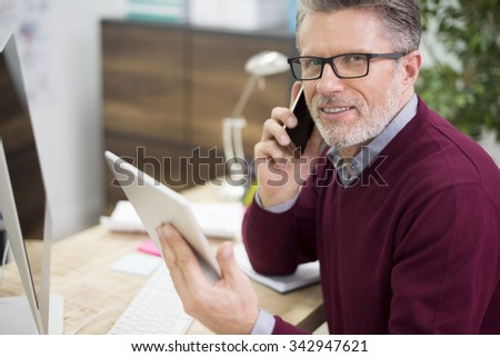 Busy man in the surrounding of technology - stock photo