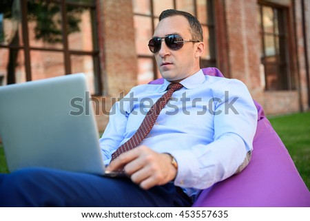 Busy man working on computer outdoors - stock photo