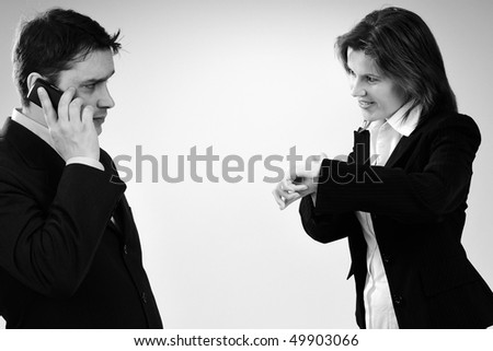 busy manager talking on cell phone and woman showing time - stock photo