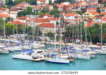 Busy marina with sail boats tied to the pier in front of an old town, Trogir, Croatia - stock photo