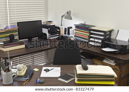 Busy, messy corner office with piles of files. - stock photo