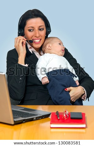Busy mother holding her baby - stock photo