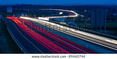 Busy Motorway at night with car lights trails - stock photo