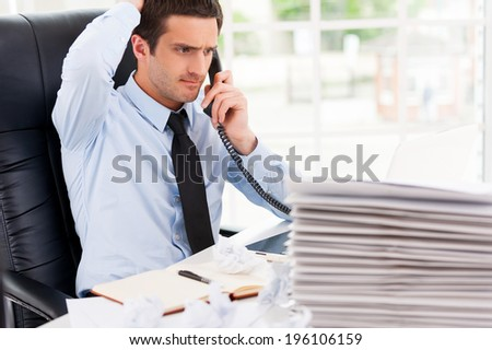 Busy office life. Frustrated young man in formalwear talking on the telephone and holding hand in hair while sitting at his working place - stock photo