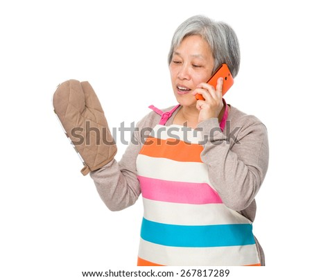 Busy old lady with kitchen apron and talk to mobile phone - stock photo