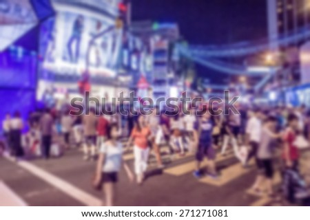 Busy people on street at night in defocused blur concept vintage color style. - stock photo