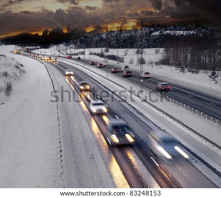 Busy road in winter evening - stock photo