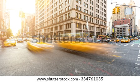 Busy road intersection in Manhattan, New York, at sunset. There are some blurred yellow cabs on foreground, and buildings, people and cars on background. Long exposure shot. Travel and city life.