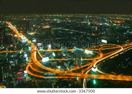 Busy road intersection in the heart of downtown Bangkok, shot at night showing car headlight trails - stock photo