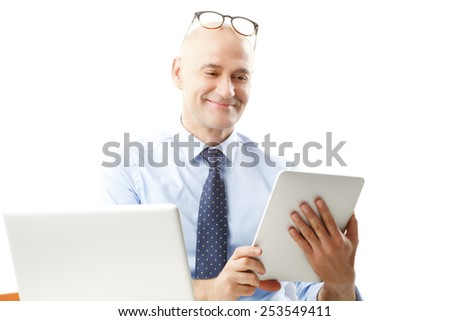 Busy sales man holding digital tablet while sitting at desk in front of computer. Isolated on white background.  - stock photo