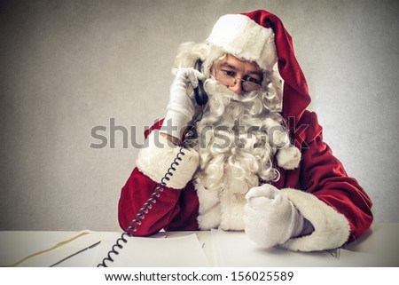busy Santa Claus talking on the phone - stock photo