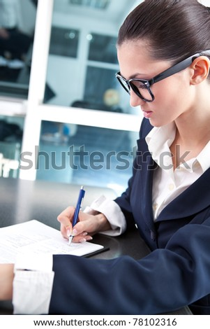 busy secretary or businesswoman writing in office - stock photo