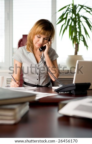 Busy secretary speaking on the phone and reading document in the office