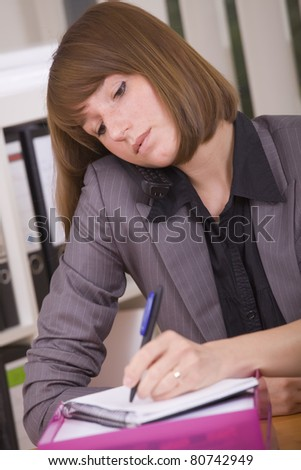 busy secretary with phone writing notice on paper