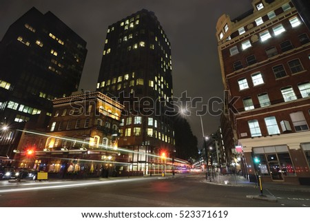 Busy street in London with bar, office buildings and blurred traffic lights