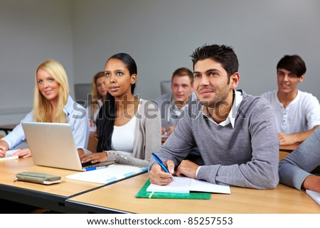 Busy students learning in a university class - stock photo