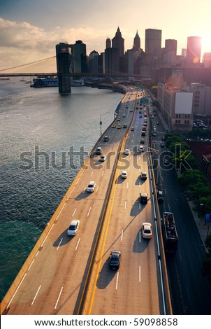 Busy traffic in New York City Manhattan with Brooklyn Bridge across Hudson River at sunset. - stock photo