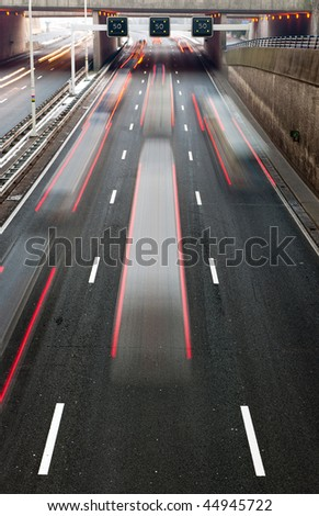 Busy traffic on a motorway with a speedlimitation ahead - stock photo