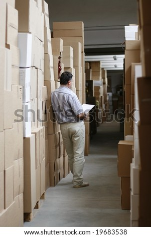 busy warehouse corridor with men working and overproduction - stock photo