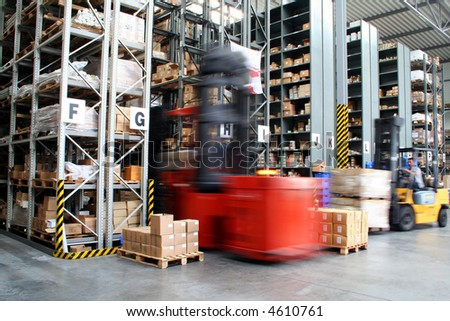 Busy warehouse with pallet trucks working - stock photo