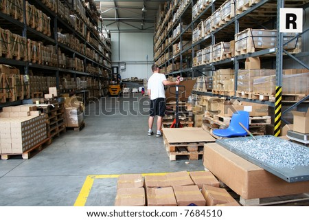 Busy warehouse with people working - stock photo