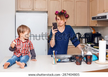 Busy white mother housewife with hair-curlers in her hair surfing Internet chatting on phone in kitchen, her child son boy sitting beside her smiling and playing on his own, crazy busy life concept - stock photo